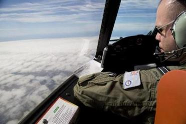 Flight Lieutenant Jayson Nichols looked out of the cockpit of a Royal Australian Air Force AP-3C Orion aircraft while searching for missing Malaysian Airlines flight MH370 over the southern Indian Ocean on Thursday.